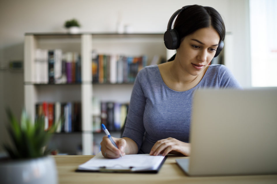 Young woman working from home with headphones in