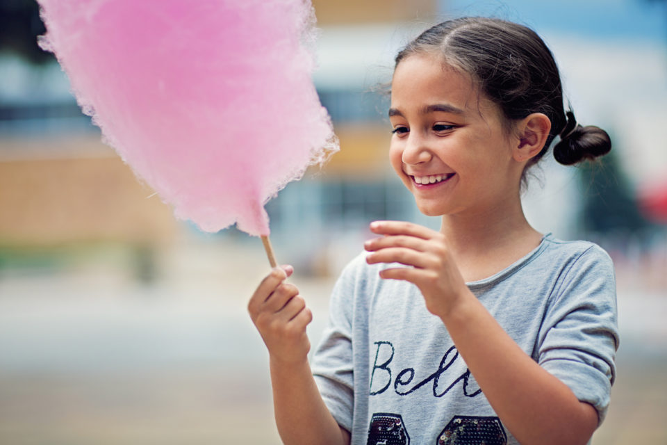 Portrait of little girl eating cotton candy