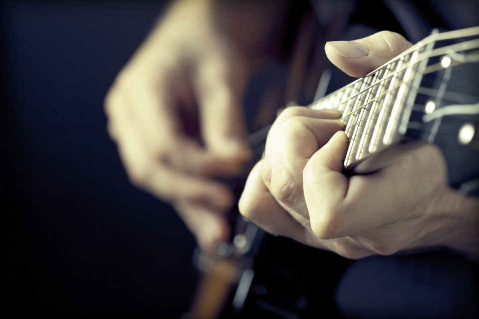 Close up on hands playing on electric guitar