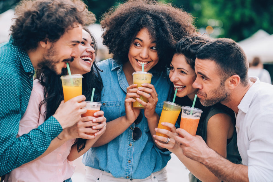 Group of friends drinking juice outdoors